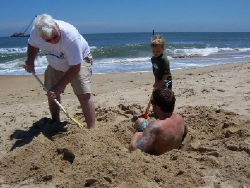 Grandpa and Cole burying Christian at the beach